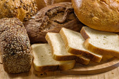 Assortment of baked bread on wood table. Fantastic range of homemade fresh bread Stock Images