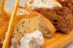 Assortment of baked bread on wooden plate Stock Photography