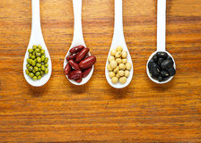 Assortment of beans in white spoon on wooden background. Mung be Royalty Free Stock Images
