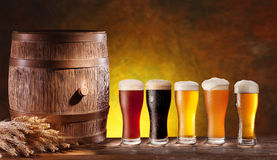 Beer glasses with a wooden barrel. Assortment of beer glasses with a wooden barrel. Background - dark yellow gradient royalty free stock photo