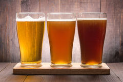 Assortment of beer glasses on a wooden table Stock Photos