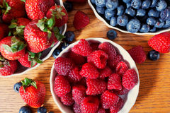 Assortment of berries, colorful ripe and fresh. Red raspberries, juicy strawberries and ripe blueberries on a wooden surface Stock Images