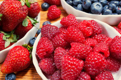 Assortment of berries, colorful ripe and fresh. Red raspberries, juicy strawberries and ripe blueberries on a wooden surface Stock Image