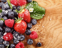 Assortment of berries over a wood table. Top-view of an assortment of berries like blueberries, raspberries and strawberries over a wood table with copy-space Stock Photography