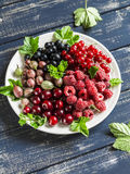 Assortment of berries - raspberries, gooseberries, red currants, cherries, black currants on a white plate on a wooden background. Stock Images