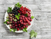 Assortment of berries - raspberries, gooseberries, red currants, cherries, black currants on a white plate on a wooden background. Stock Photo