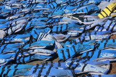 An assortment of blue life vests laying on the ground. Blue life vests spread out across the ground in a random pattern with one yellow life vest in the picture royalty free stock photos