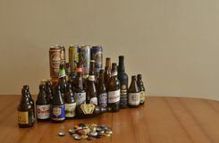 Assortment of beer bottles and cans on table. Drinking at home.
