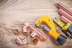 Assortment of brass water pipe cutter fixtures tape line on wood Royalty Free Stock Image