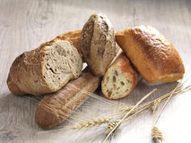 Assortment of bread. An assortment of baked bread on a wooden surface stock photos