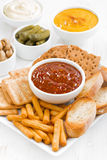 Assortment breads, crackers and sauces on white table Royalty Free Stock Photography