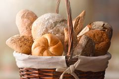Assortment of breads over a wicker basket close up. Assortment of breads over a wicker basket in a rustic kitchen. Horizontal composition. Front view stock image