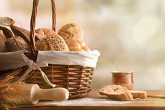 Assortment of breads over a wicker basket in kitchen detail. Assortment of breads over a wicker basket on a table in a rustic kitchen. Horizontal composition stock photo