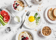 Assortment of breakfast - fried egg, fresh vegetables, oatmeal with berries, cottage cheese, yogurt and berries, homemade granola royalty free stock images