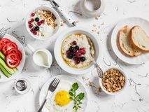 Assortment of breakfast - oatmeal with berries, fried egg, fresh vegetables, cottage cheese, yogurt and berries, homemade granola Royalty Free Stock Photos