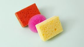 Assortment of bright scouring sponges on green surface.Concept of products for house cleaning.Different colors royalty free stock photo