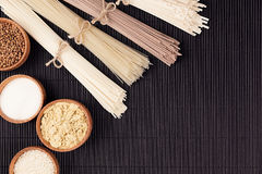 Assortment of bundles raw noodles with ingredient in wooden bowls on black striped mat background with copy space, top view. Royalty Free Stock Image