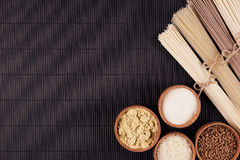 Assortment of bundles raw noodles with ingredient in wooden bowls on black striped mat background with copy space, top view. Stock Photos