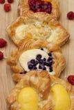 Assortment of cheese danishes puff pastry with blackberries, vanilla custard, cherry jam and fresh raspberries.  Royalty Free Stock Photography