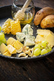 Assortment of cheese with fruits, berries, honey Stock Photo