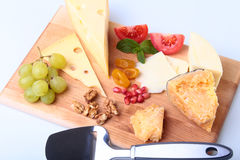 Assortment of cheese with fruits, grapes, nuts and cheese knife on a wooden serving tray. Royalty Free Stock Photography