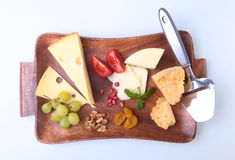 Assortment of cheese with fruits, grapes, nuts and cheese knife on a wooden serving tray. Royalty Free Stock Images