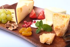 Assortment of cheese with fruits, grapes, nuts and cheese knife on a wooden serving tray. Royalty Free Stock Image