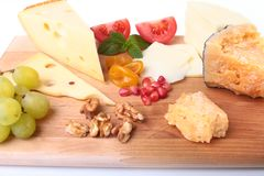 Assortment of cheese with fruits, grapes, nuts and cheese knife on a wooden serving tray. Royalty Free Stock Photos