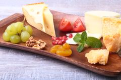 Assortment of cheese with fruits, grapes, nuts and cheese knife on a wooden serving tray. Stock Images