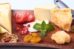 Assortment of cheese with fruits, grapes, nuts and cheese knife on a wooden serving tray. Stock Photography