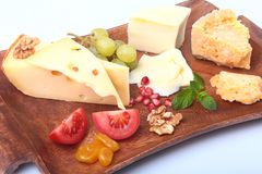 Assortment of cheese with fruits, grapes, nuts and cheese knife on a wooden serving tray. Stock Image