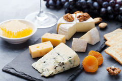 Assortment of cheese with honey, nuts and grape on a modern cutting board slate background. Stock Photography