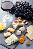 Assortment of cheese with honey, nuts and grape on a modern cutting board slate background. Royalty Free Stock Photography
