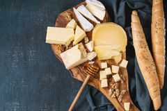 Assortment of cheese on wooden board. Cheese plate. Assortment of cheese with walnuts, honey and bread on olive wood serving board with textile over dark blue Stock Photo