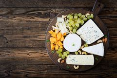Assortment of cheeses. Camembert, dor blu, brie on a wooden background stock photography