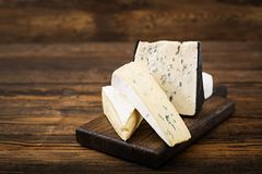 Assortment of cheeses. Camembert, dor blu, brie on a wooden background Royalty Free Stock Photos