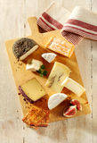 Assortment of cheeses on a cheeseboard. Assortment of soft and semi-hard cheeses on a cheeseboard with sliced fresh figs and toast for a gourmet appetizer to a Royalty Free Stock Image