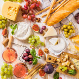Assortment of cheeses, fruits, breads, wine and snacks on white Stock Photo