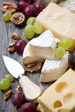 Assortment of cheeses, grapes and walnuts on a wooden background Stock Image