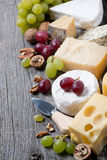 Assortment of cheeses, grapes and walnuts on a wooden background Stock Images