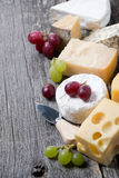 Assortment of cheeses and grapes on a wooden board Royalty Free Stock Photo