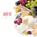 Assortment of cheeses, red and green grapes, crackers and wine Stock Photos
