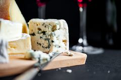 Assortment of cheeses on a wooden plate and two wine glasses. stock photography