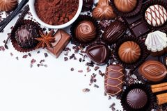 Assortment of chocolate candies, cocoa products and spices on white background. Top view. Copy space. Royalty Free Stock Image