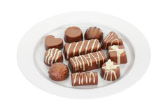 Assortment of chocolate candies on the white platter, 3D renderi Royalty Free Stock Photography