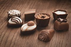 Assortment of chocolates on wooden background stock images