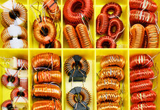Assortment of choke coils in a yellow box royalty free stock images