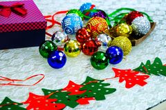 Assortment of Christmas balls. On a table with a present box and some ribbons Stock Photos
