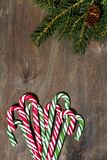 assortment of christmas sugar candies and fir branches on grey wooden background stock photos