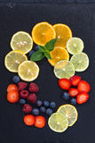 Assortment of citrus and fresh berries on a dark background Royalty Free Stock Image